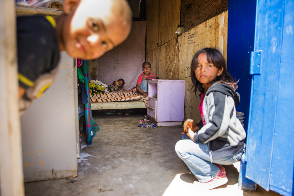 humanitarian documentary photo of four Mexican children playing in their small home