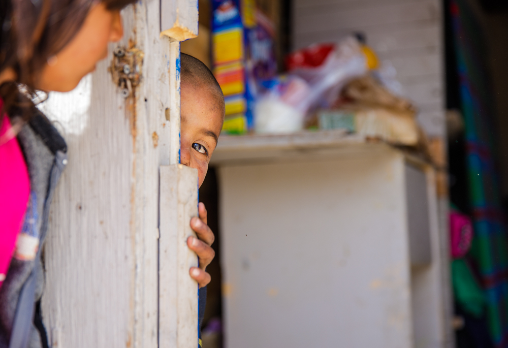 Mexican boy peeking around the corner toward his sister