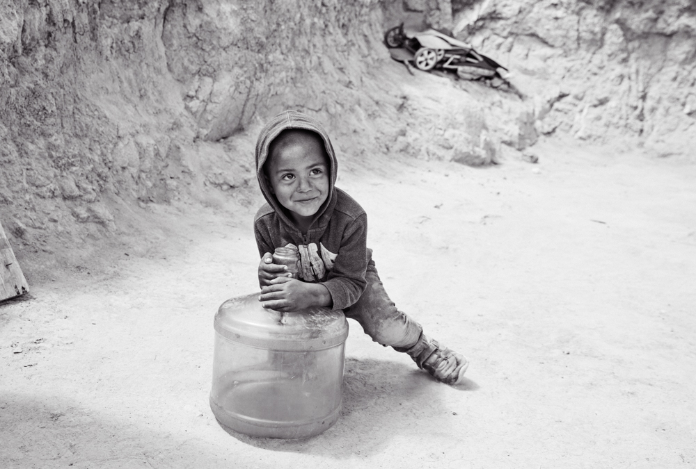black and white photo of a small boy in Mexcio playing with a 5 gallon water jug