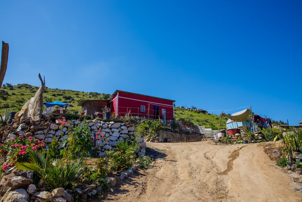 small but beautiful red Mexican house on a hillside with blue sky above