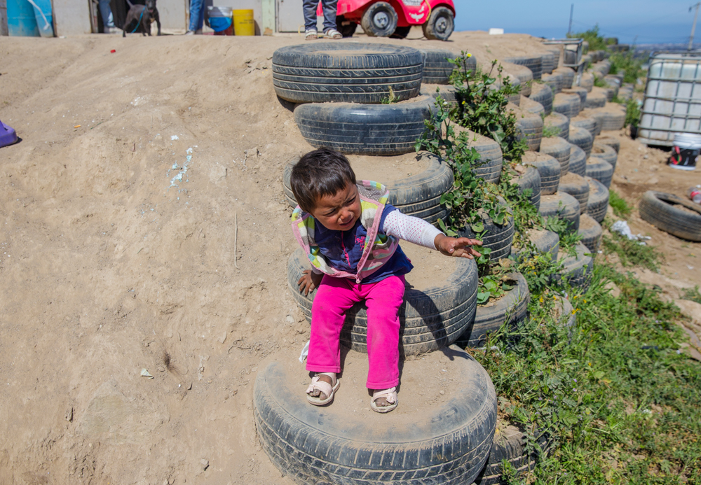 Mexican toddler playing on a tire