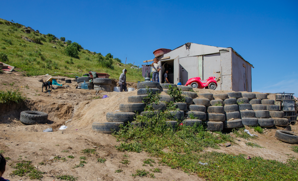 humanitarian documentary photo of Ochoa family home in Ensenada Mexico held up by tires on a hillside