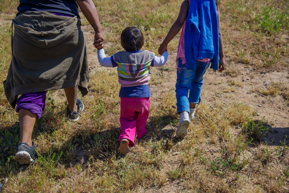 toddler girl walking through rough grass with an adult and an older child