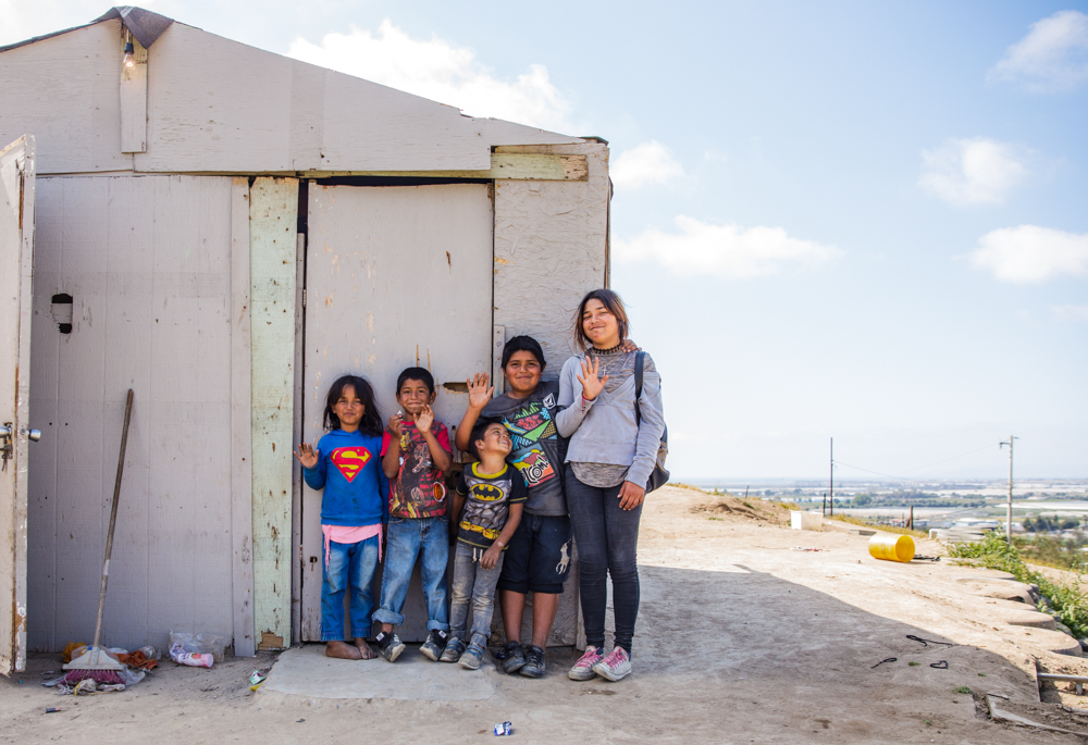 humanitarian documentary photo of a group of children siblings standing in front of their home in Ensenada Mexico